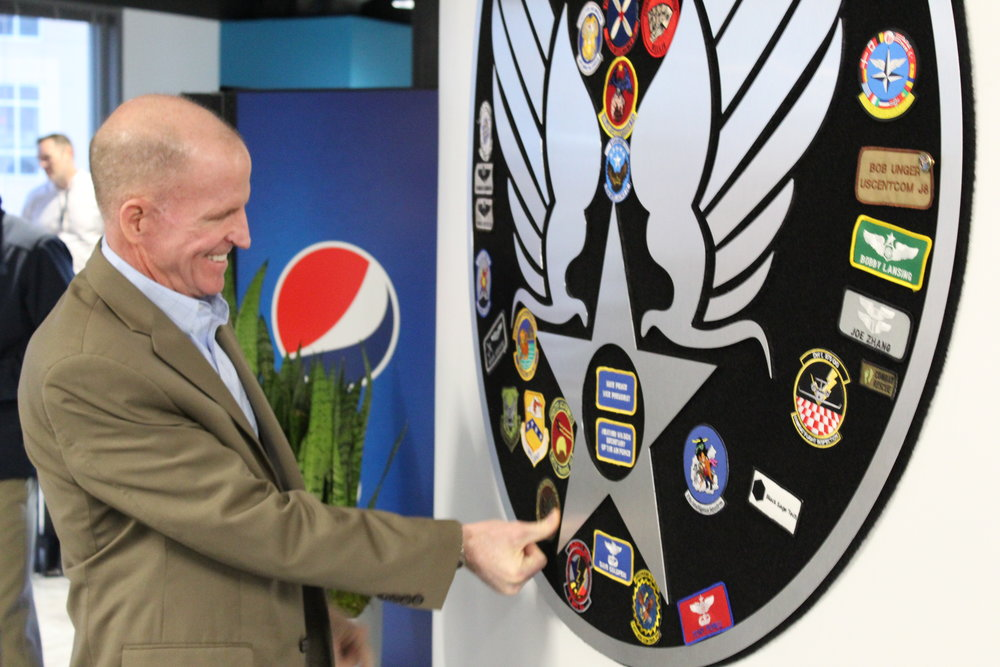 """Vice Chief of the Air Force Gen. Stephen W. """"Seve"""" Wilson adds his insignia to the """"patch wall"""" at the AFWERX Vegas Innovation Hub. Wilson and other senior Air Force leaders informally met with approximately 60 airmen and AFWERX personnel, launching a 4-day facilitated workshop. Airmen were tasked with identifying opportunities for innovation in training rotary-wing, battle management, and remotely-piloted aircraft personnel."""