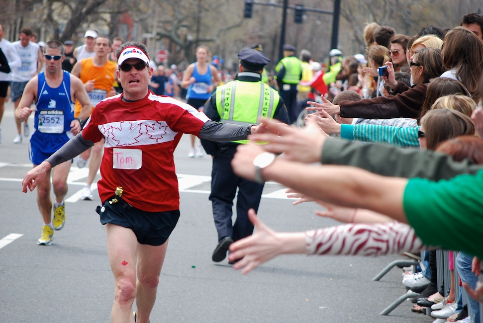 Boston, Mass. - April 20, 2009: A runner gets encouragement and high-fives from spectators at Audubon Circle, the last stretch of the Boston Marathon. Photo by Andrew Bisdale.