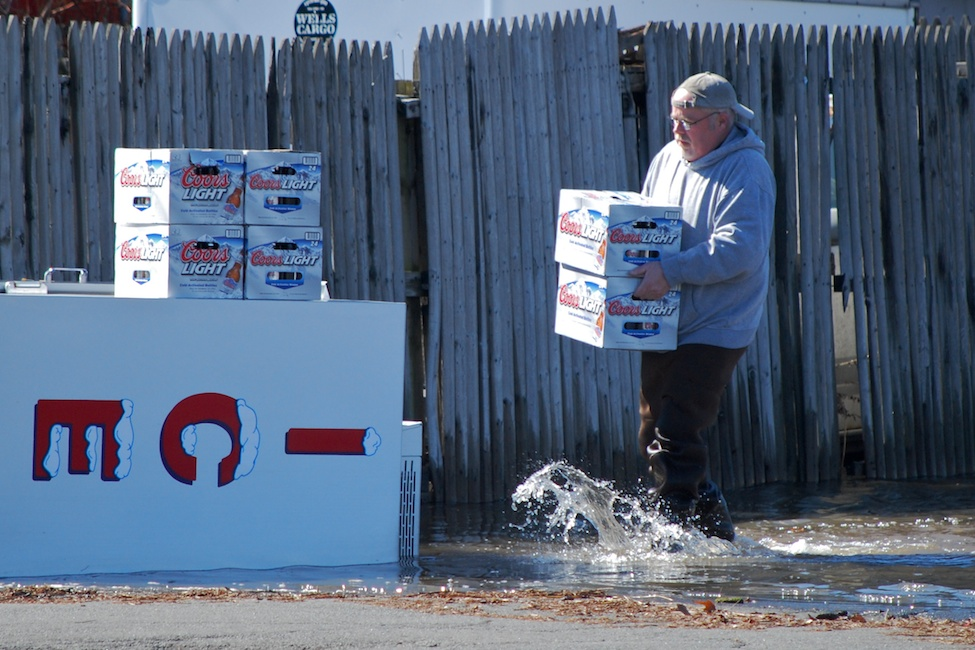 West Nyack, NY - March 7, 2011: A man salvages beers from a liquor store near a flooded highway by The Palisades Mall.  Flooded highways caused major traffic problems all over the Tri-State Area.  Photo by Andrew Bisdale.