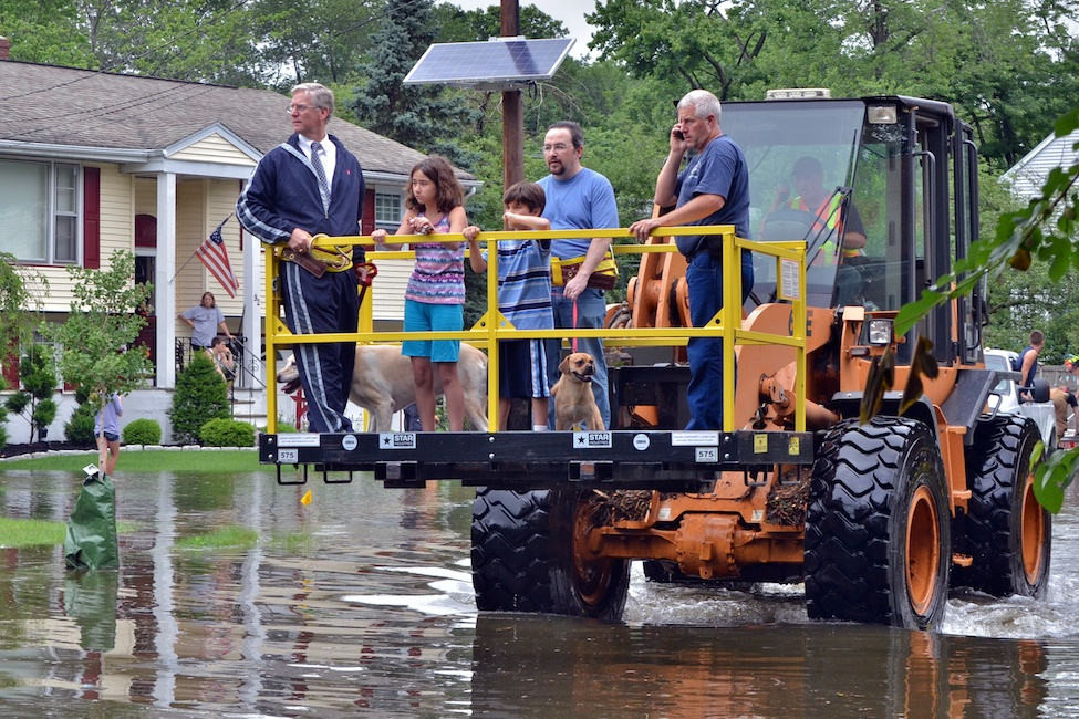 Westwood, NJ - June 23, 2011: Borough administrator Robert Hoffmann (left) and Westwood Firefighter Kevin Woods (right) assist Robert Ouellette in evacuating his family (center) after a broken dam caused the third major flood of the year.  Photo by Andrew Bisdale.