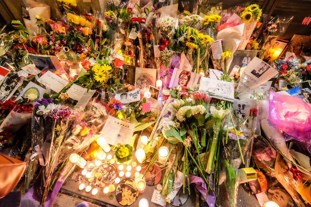 New York, NY - Jan. 11, 2016: Mourners leave candles, flowers and other tributes outside David Bowie's apartment at an impromptu vigil following the singer's death.