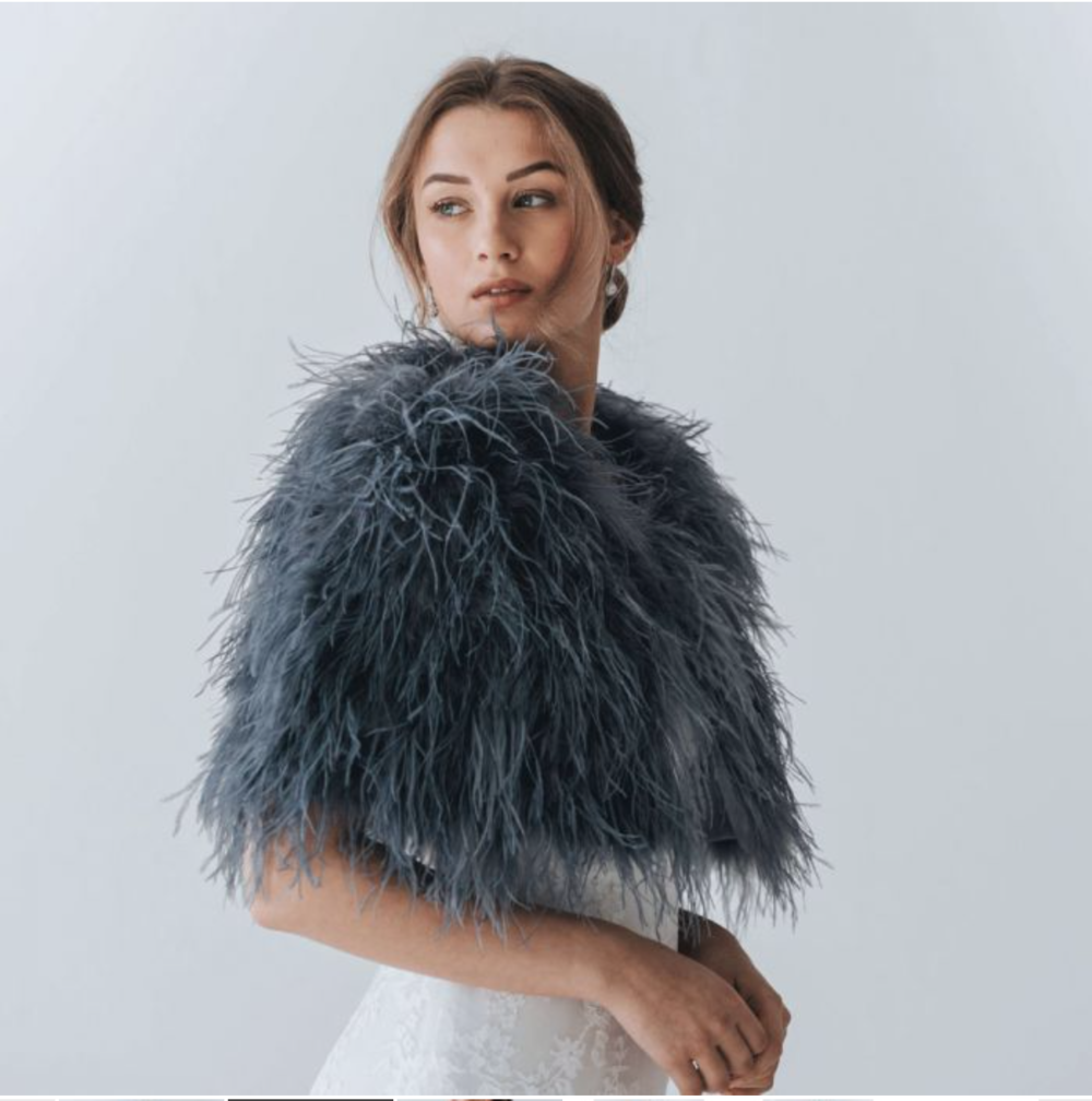 The Jacket - If you're getting married in winter you're going to need something to keep you from catching pneumonia on the big day. Needless to say, a white jacket isn't that useful for any day bar your wedding day so why not go for something dramatic in a darker colour? A faux-fur or feather cape is perfect for adding glamour to your wedding dress and any other evening gown you wear afterwards.Find this cape by Aria here