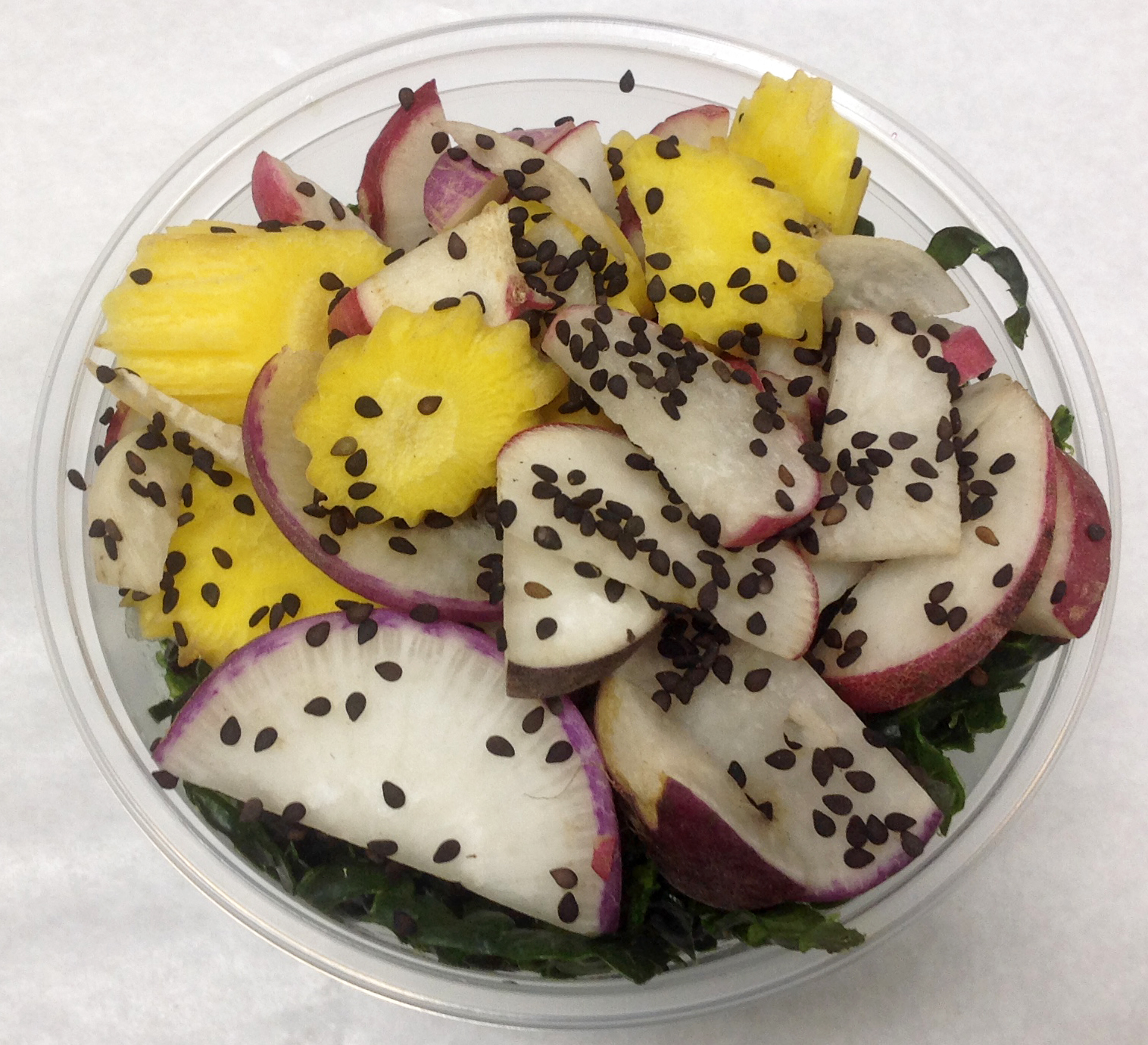 Lacinato kale salad with red radish, colorful heirloom carrots and black sesame seeds.