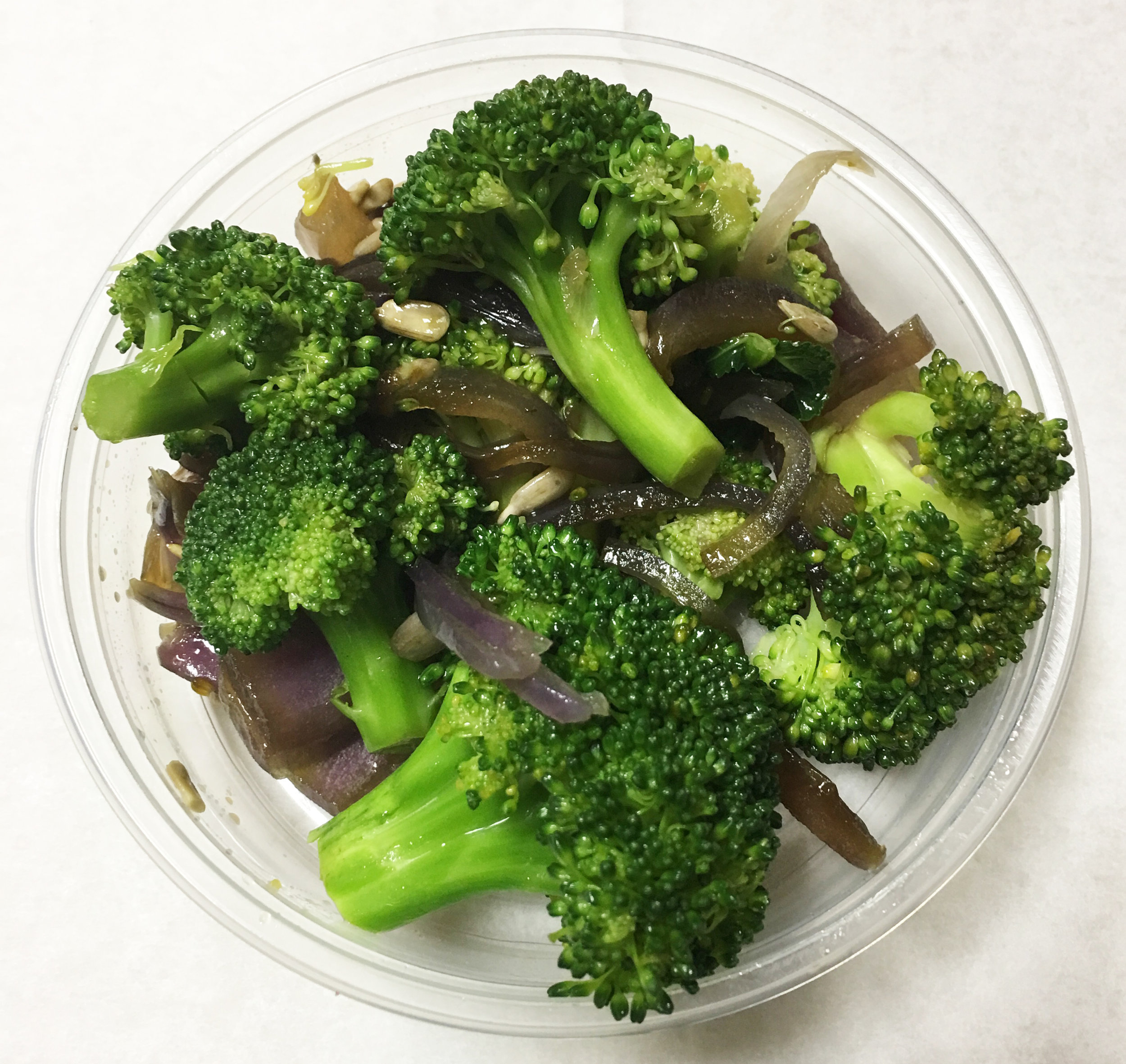 Boiled broccoli with red onion and sunflower seeds.
