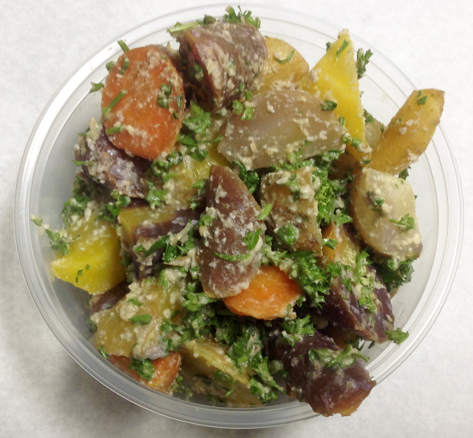 Boiled salad of colorful heirloom carrots with parsley and garlic sauce.