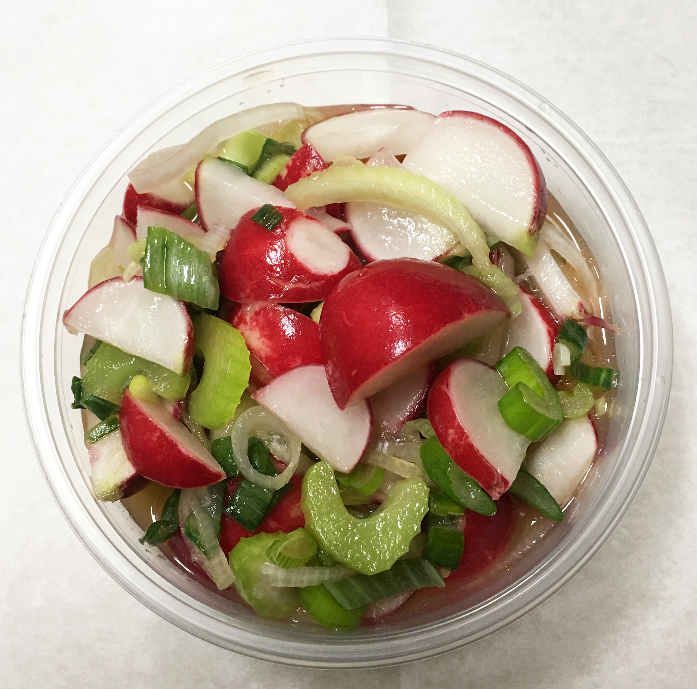Marinated red radish, celery and spring onion tops in a lemon, orange citrus dressing.