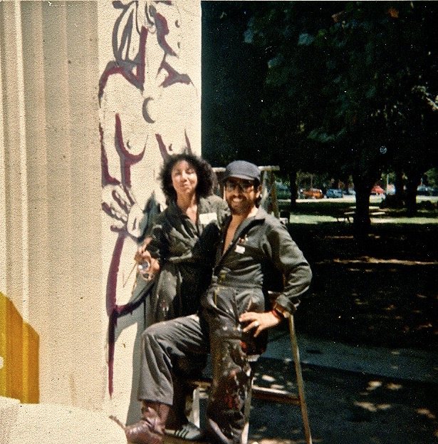 RCAF Artists Lorraine García-Nakata and José Montoya, 1977, during original painting of South Side Mural, Sacramento, California. Standing in front of initial rendering of Lorraine's sections of the South Side Mural