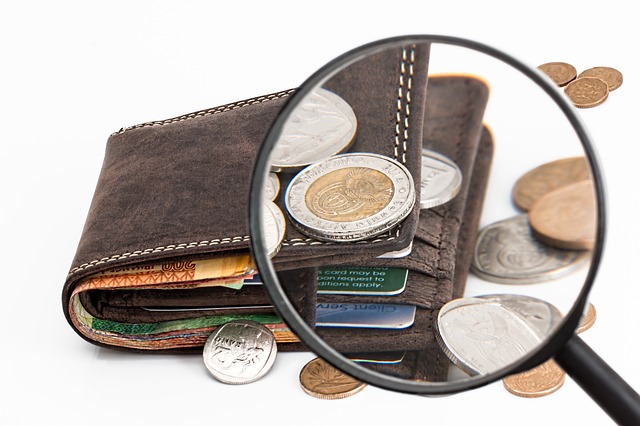 Wallet with coins, cards, and cash viewed through the lens of a magnifying glass.