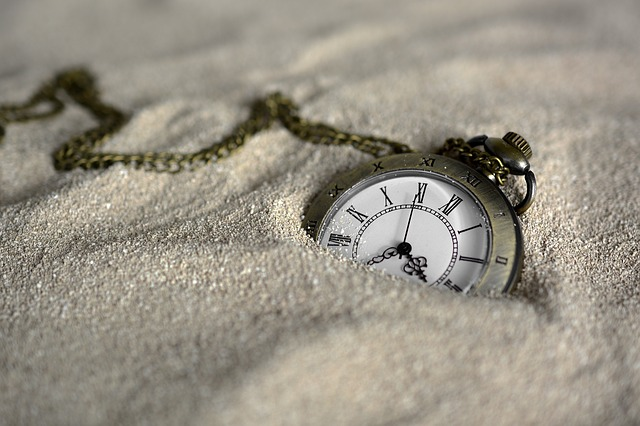 Pocket watch sinking into a pile of sand.