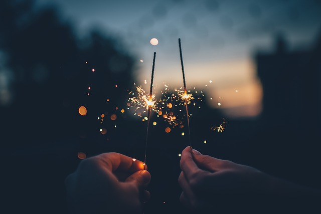 Two people's hands holding sparklers for New Year's Eve celebration.