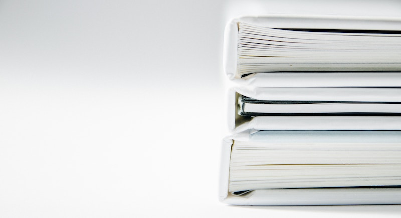 Stack of white binders filled with paper documents.