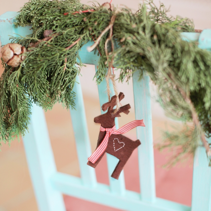 Reindeer ornament hanging precariously from a piece of twine wrapped around a holiday wreath.