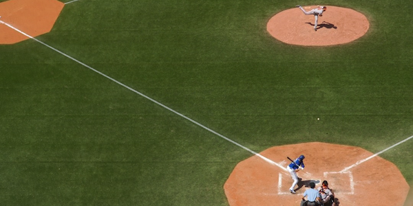 Baseball player throwing a pitch towards the hitter on a baseball field.