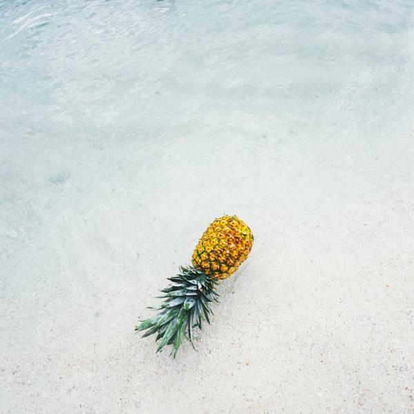 A pineapple on a beach.