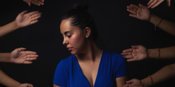 Woman surrounded by outstretched hands against a black background.