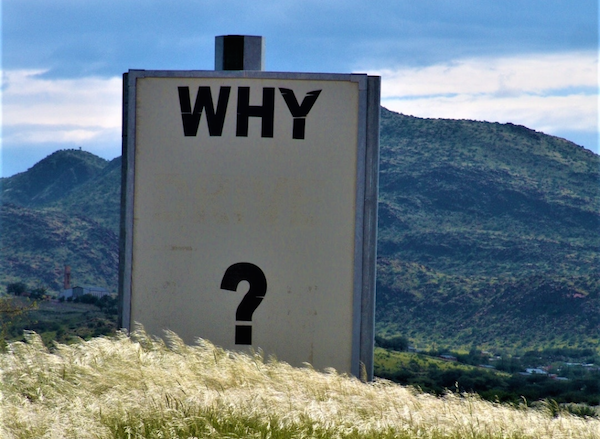 "A sign on a hill with the text, ""Why?"""