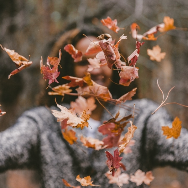 Woman in a gray sweater tossing crisp fall leaves into the air.