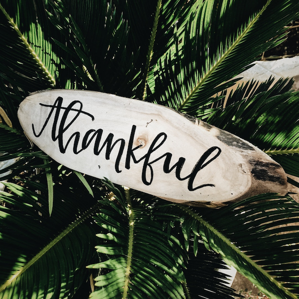 "Hand-lettered sign on a piece of wood with the text ""Thankful."""