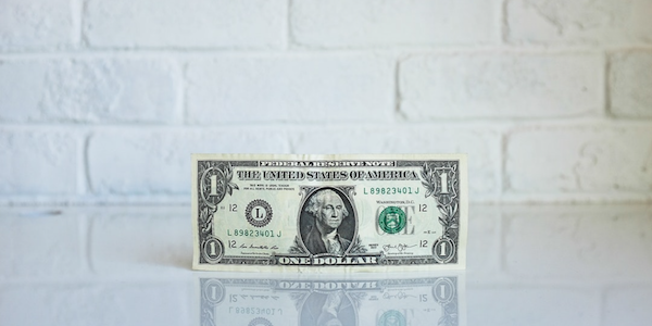 US dollar bill against a white brick background.