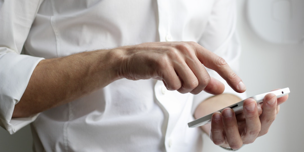 Man in a white shirt holding a smartphone.