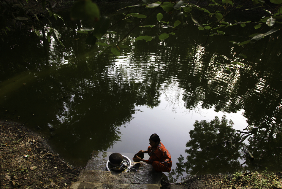 Tohomina Akter washes pots and dishes in a pond near her home in Char Baria village, Barisal, Bangladesh, on the morning of Thursday, April 19, 2012.