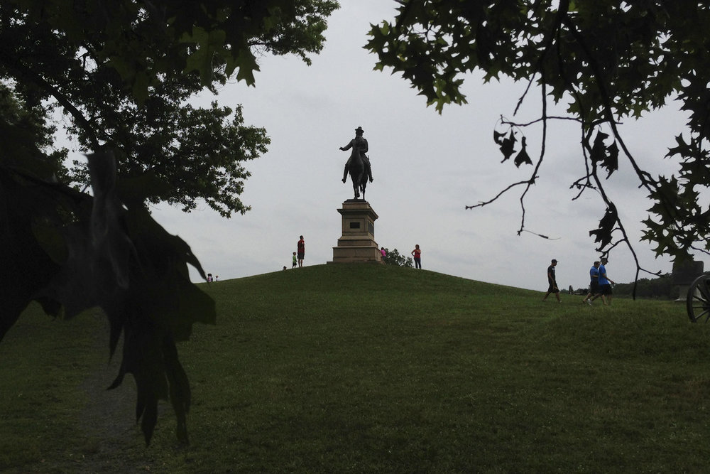 Visitors to Gettysburg National Battlefield Park are dwarfed by a statue near the Soldier's National Cemetery.