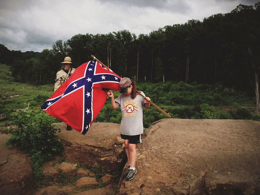 With a shoulder draped rebel flag and a toy gun in her hand, a young girl carefully makes the way down the time and traffic smoothed rocks of Devil's Den while playing war.