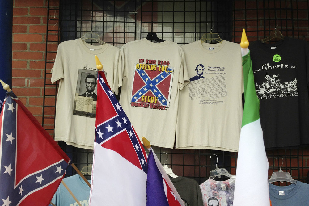 "A tourist trap lures with overpriced t-shirts featuring US President Abraham Lincoln and his Gettysburg Address alongside multiple novelties featuring the Confederate flag and a shirt advertising The Ghosts of Gettysburg. The shirt in the middle reads, ""If this flag offends you … study American history."""