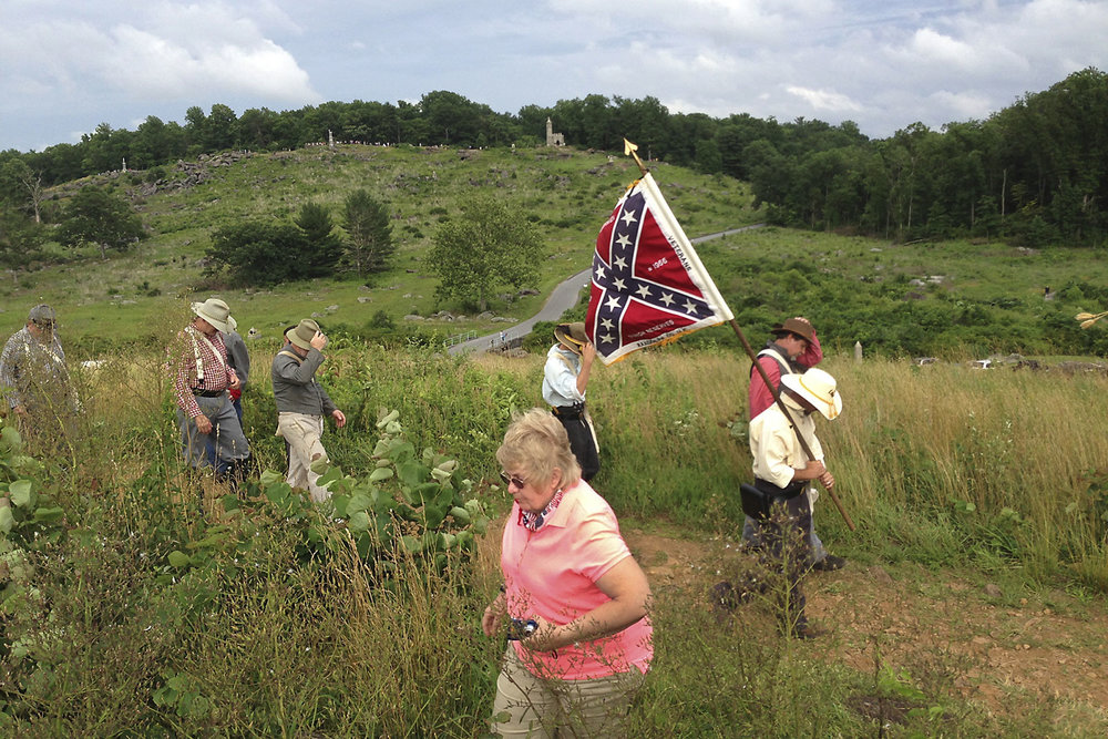 A wind gust builds strength as it rolls over the 'awful, awful rocks' of the Devil's Den, tugs on a group of Confederate reenactors hats and tears at that flag.