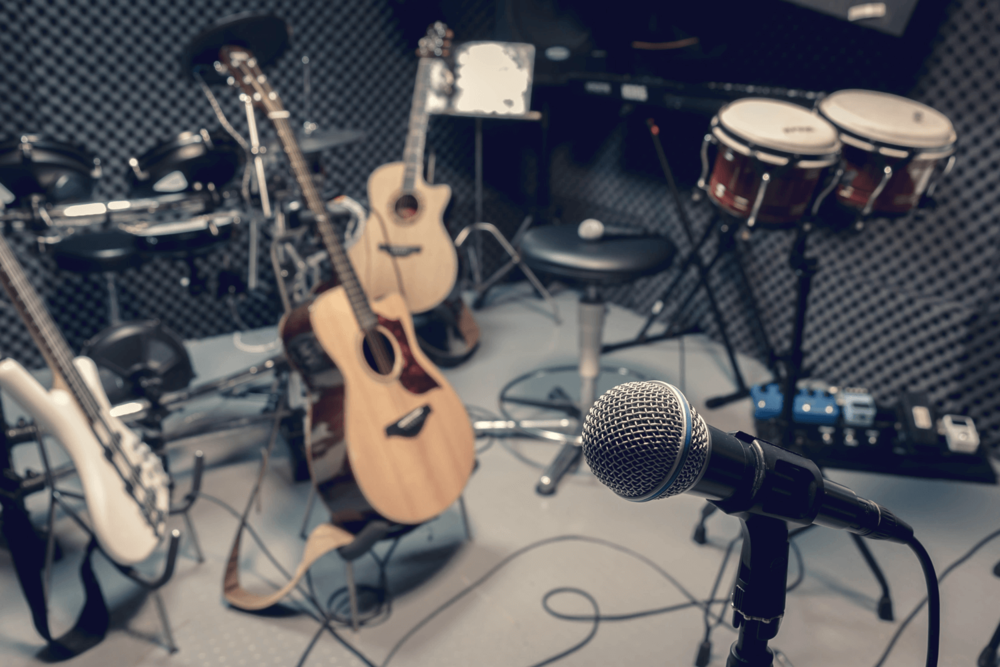 stock-photo-selective-focus-microphone-and-blur-musical-equipment-guitar-bass-drum-piano-background-346418642.jpg