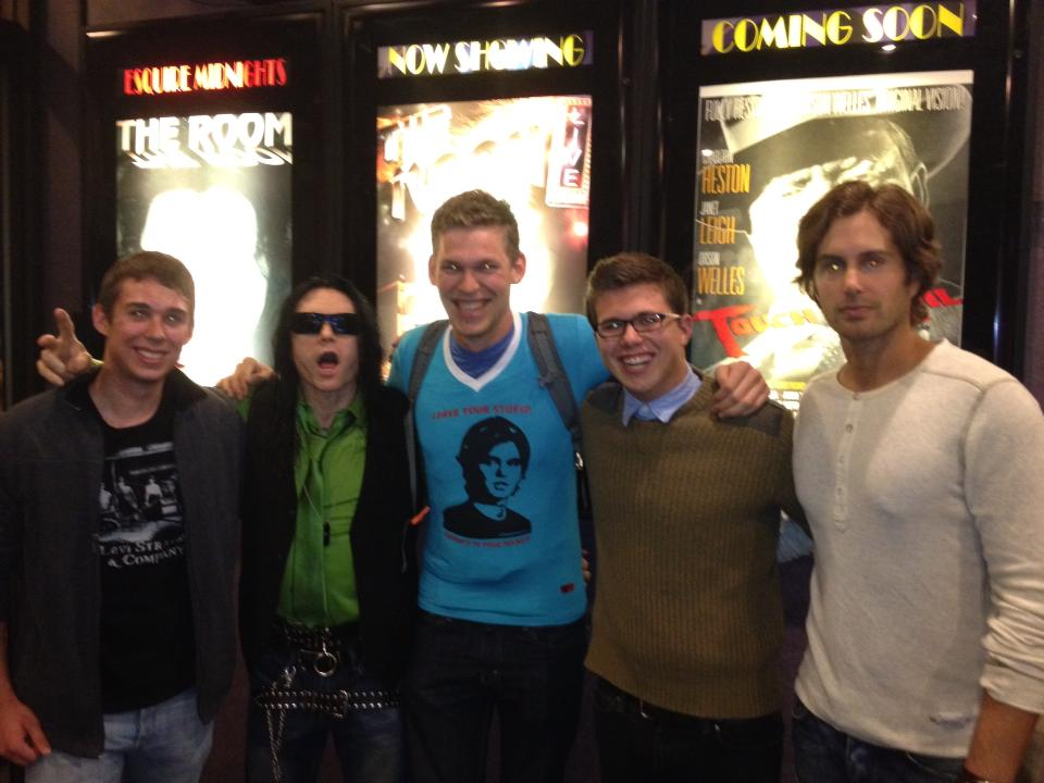 """Oh, Hi Mark… - One time Chris and I went to a movie theatre in Denver to watch the room, to my surprise Tommy Wiseau and Sestero were there. Tommy took a picture with me where he was choking me, he offered me his underwear (I'm pretty sure it was a new brand he was starting, not the pair he was wearing, but honestly I can't be sure). It was… quite the experience.Also, did you know that I was in a movie that Vice Magazine called """"The Room of 2014""""? Yep, it was called """"The Lock-In"""" and it was awful."""