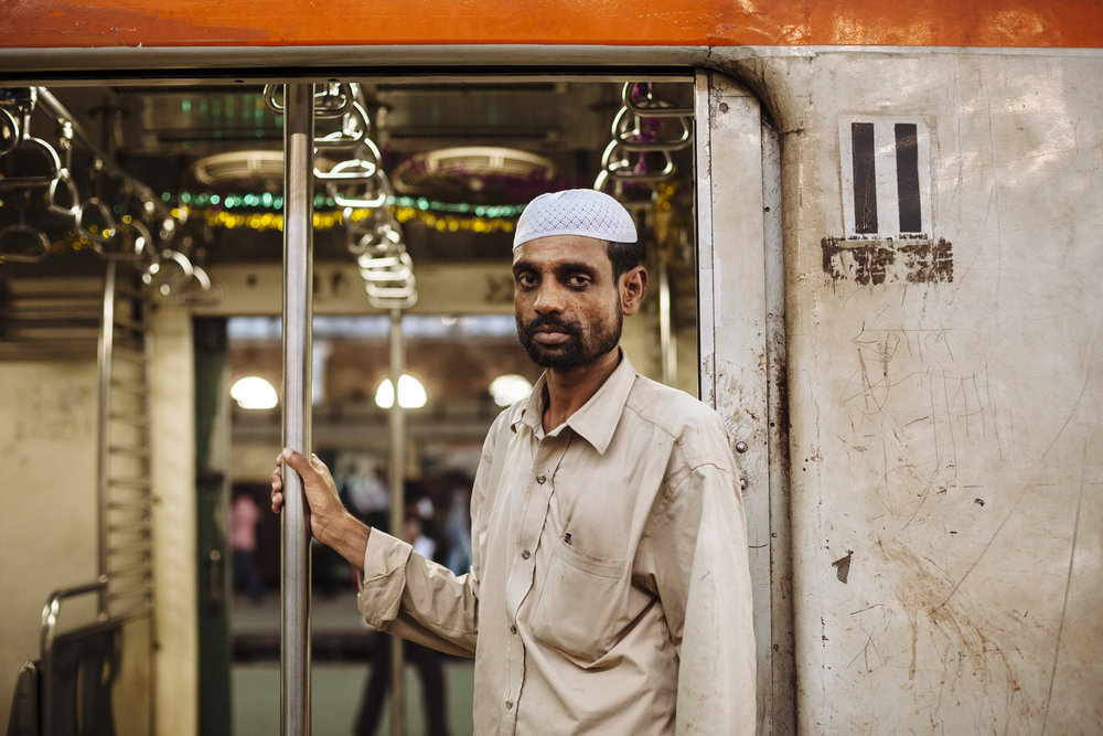 A man stands in the doorway of a commuter train at Chhatrapati Shivaji Terminus in Mumbai, India, Wednesday, Oct. 27, 2010.