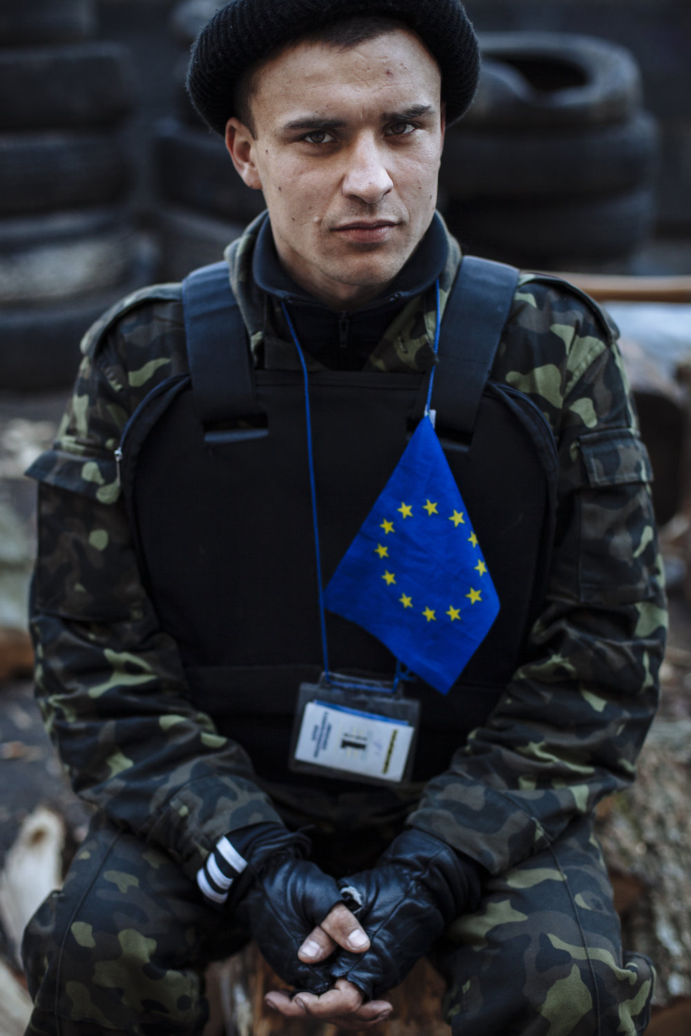 A self defense volunteer with a European Union flag affixed to his protective vest guards a barricade in Kiev's Independence Square, Ukraine, Tuesday, March 11, 2014. (AP Photo/David Azia)