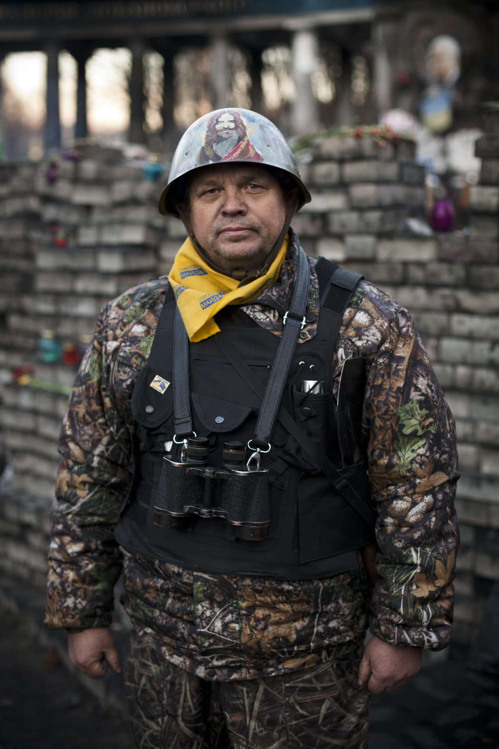 A member of a self defense volunteer group poses for a photograph next to a barricade located near the entrance to the Dynamo Kyiv soccer club stadium in Kiev's Independence Square, Ukraine, Wednesday, March 12, 2014. (AP Photo/David Azia)