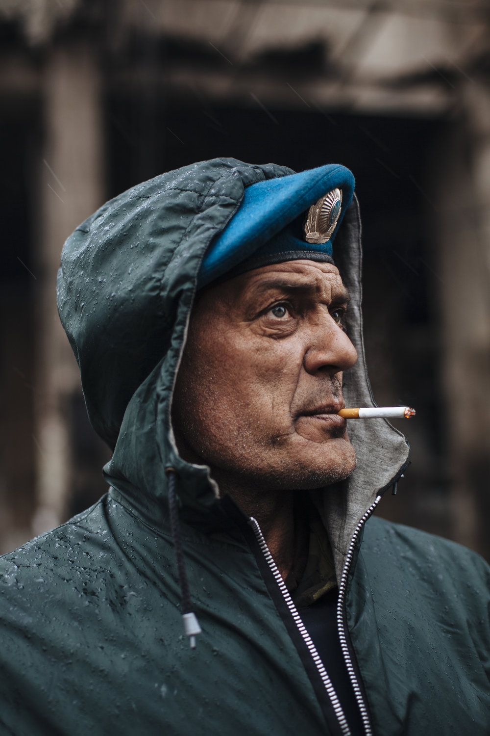 Dima, a member of a volunteer self defense group, smokes a cigarette during a rainfall in Kiev's Independence Square, Ukraine, Sunday, March 16, 2014. (AP Photo/David Azia)