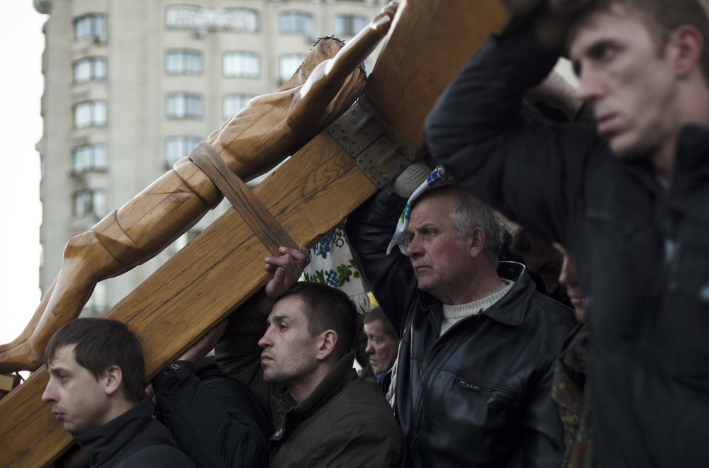 Men prop up a wooden cross during a religious service held to commemorate those killed in clashes which took place in late February near Kiev's Independence Square, Ukraine, Wednesday, March 12, 2014. (AP Photo/David Azia)