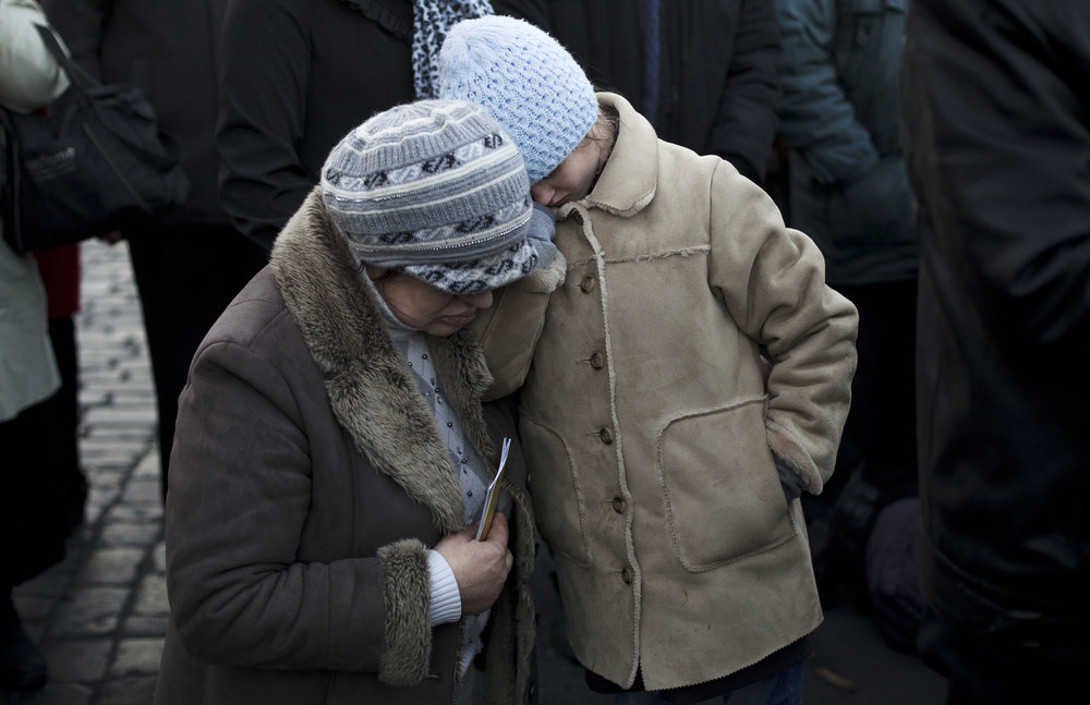 A woman and child pray during a religious service next to a memorial to people killed in clashes which took place in late February, near Kiev's Independence Square, Ukraine, Wednesday, March 12, 2014. (AP Photo/David Azia)