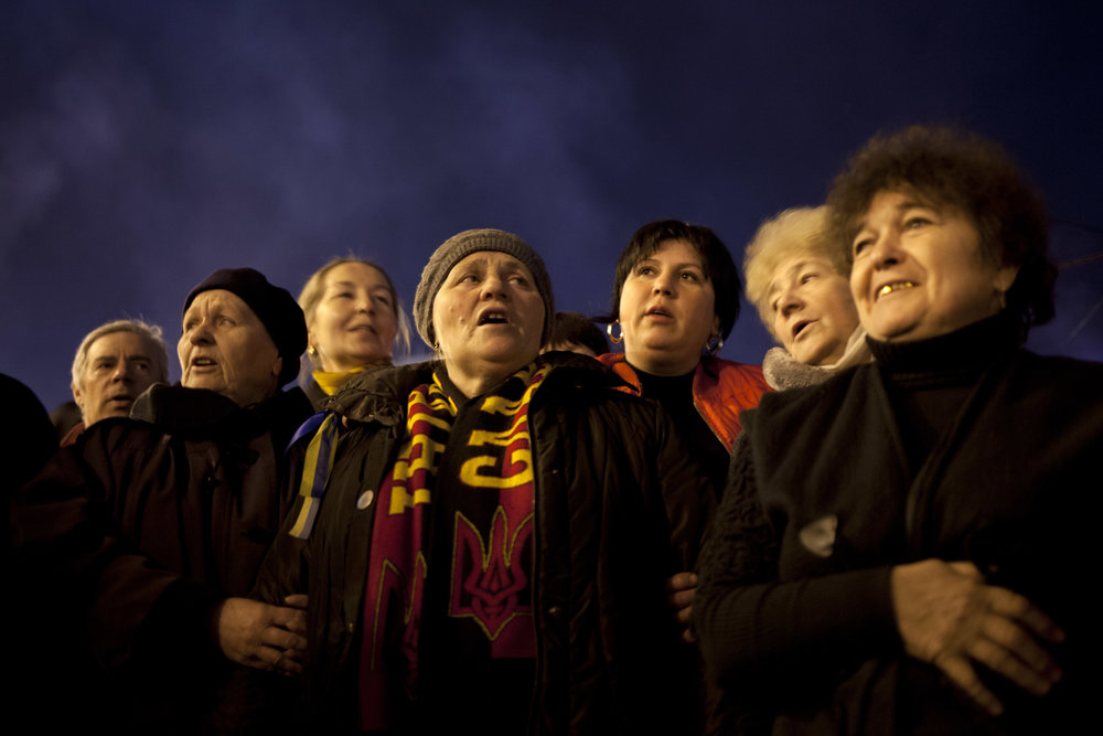 Ukrainian men and women sing the national anthem in Kiev's Independence Square, Ukraine, Saturday, March 8, 2014. (AP Photo/David Azia)
