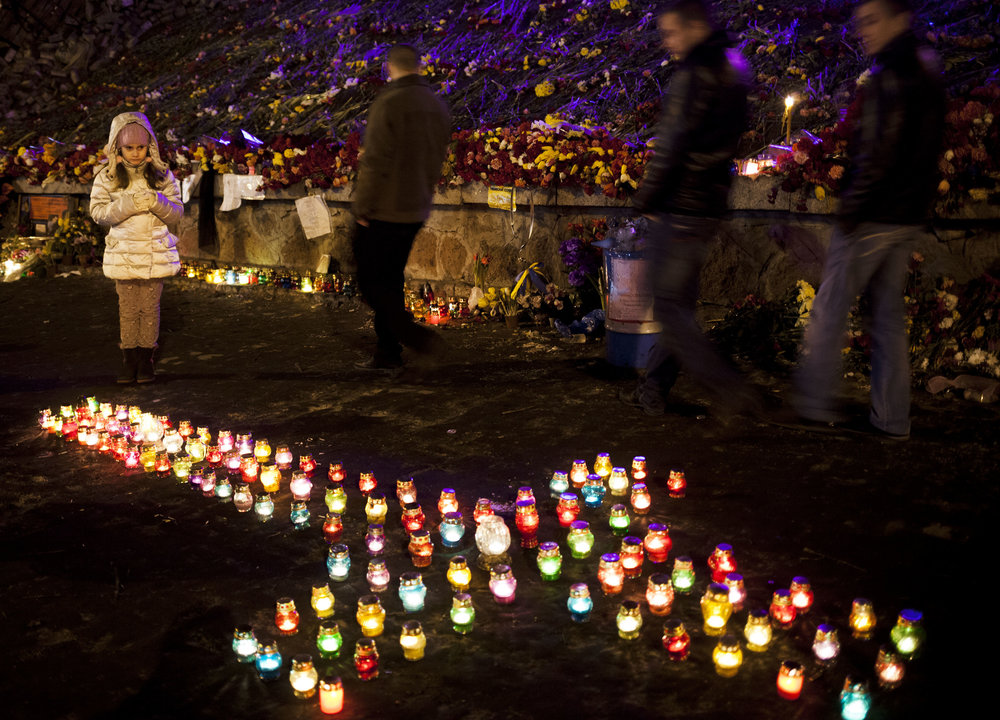 A young girl looks at candles arranged in the shape of a cross, part of a memorial to those who died in clashes which took place in late February, in Kiev's Independence Square, Ukraine, Saturday, March 8, 2014. (AP Photo/David Azia)