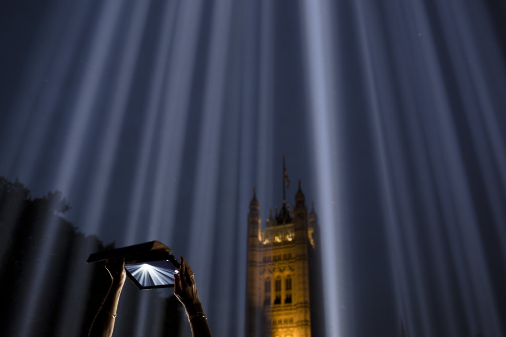 "A woman uses a tablet to photograph shafts of light piercing the night sky at an installation entitled ""Spectra"" by Japanese artist Ryoji Ikeda outside the Houses of Parliament, London, Tuesday, Aug. 5, 2014. (AP Photo/David Azia)"