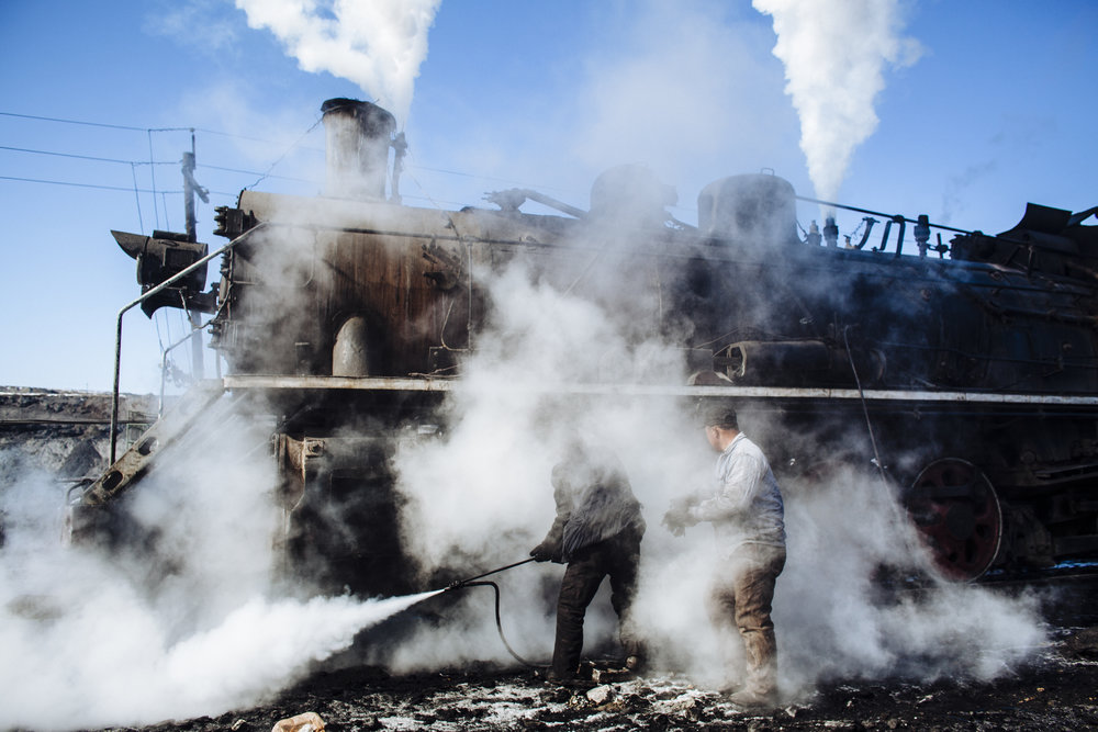 Workers use steam to clear ice from a locomotive inside the opencast coal mine in Zhalainuer, Inner Mongolia, China, Monday, March 23, 2009.