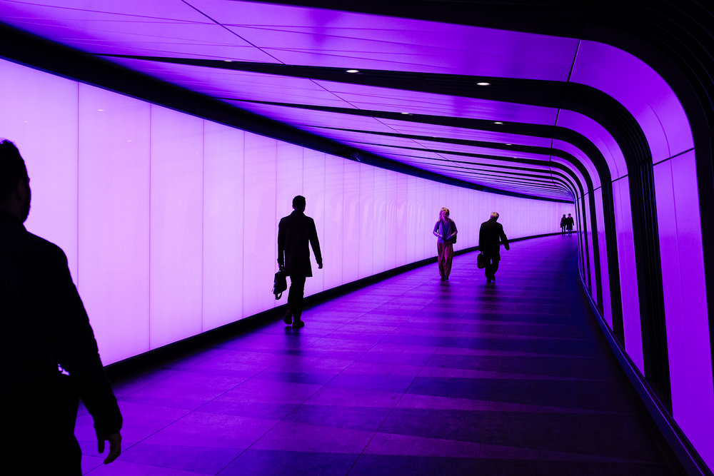 People walk through an underground passage leading out of King's Cross and St. Pancras underground tube station, London, Tuesday, May 5, 2015.