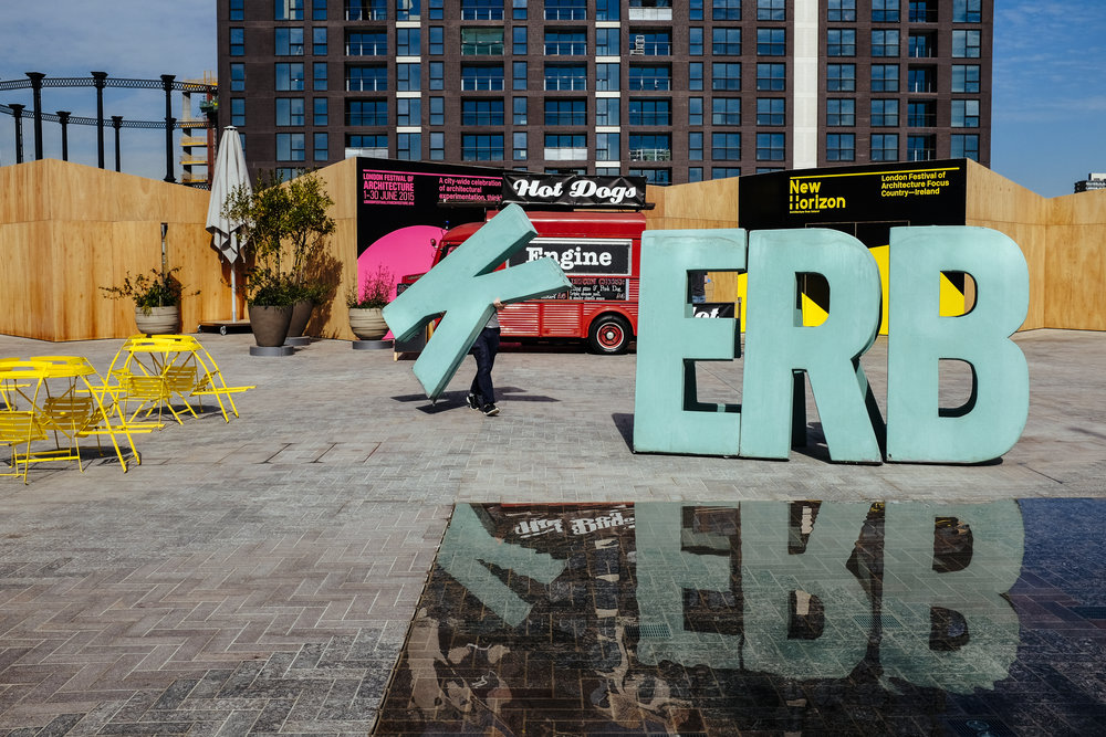 Ian, who works for Kerb, an organization that helps turn public spaces over to traders selling food, carries a letter to spell out Kerb as he prepares for traders to arrive in Cubitt Square, King's Cross, London, Thursday, June 4, 2015.