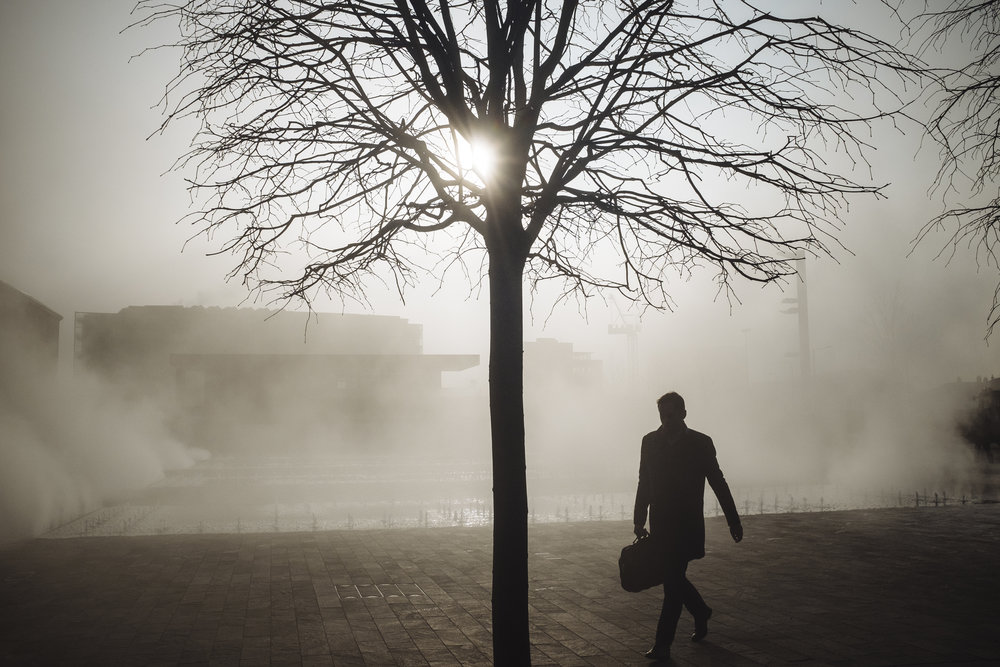 A pedestrian walks through steam rising from the fountains on Granary Square, King's Cross, London, England, Friday, March 11, 2016.