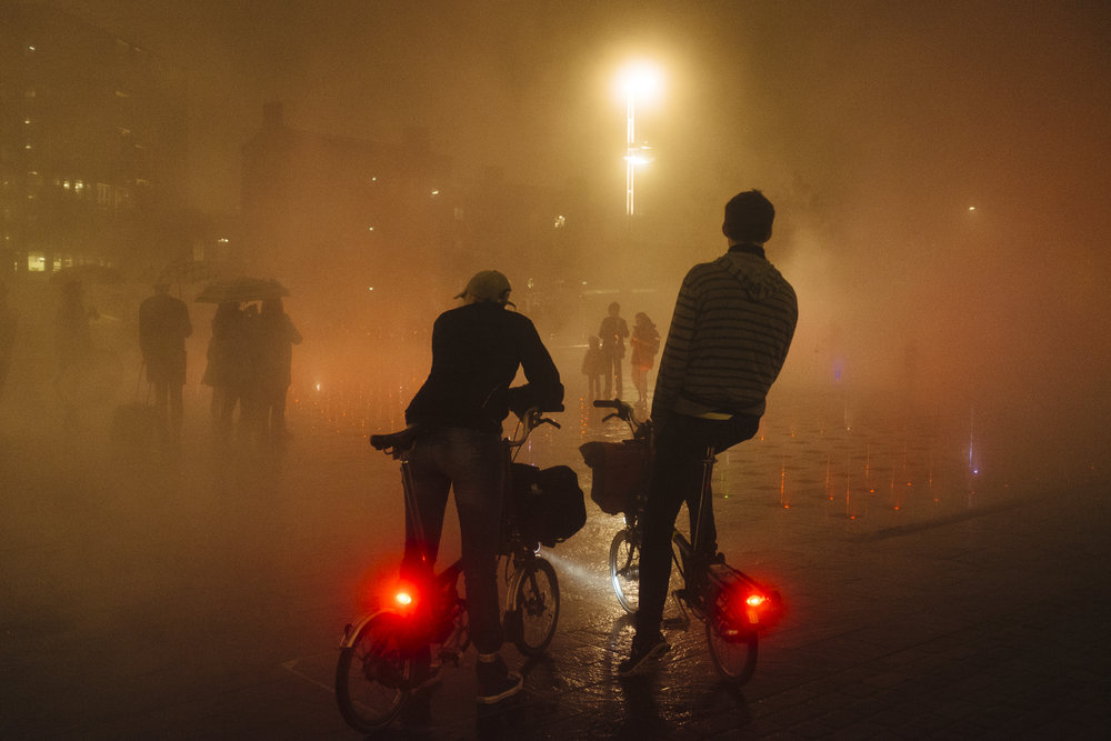Men on Brompton bicycles look at people walking through the mist rising from the fountains at Granary Square, London, England, Saturday, Nov. 12, 2016.