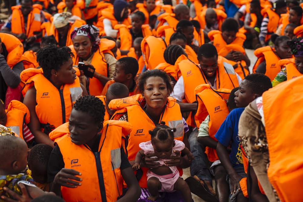 Ivorian refugees, wearing safety vests, sit aboard a UNHCR ferry as they are transported across the Cavalla River from Maryland, Liberia to Prollo, Bas-Sassandra District, Côte d'Ivoire.