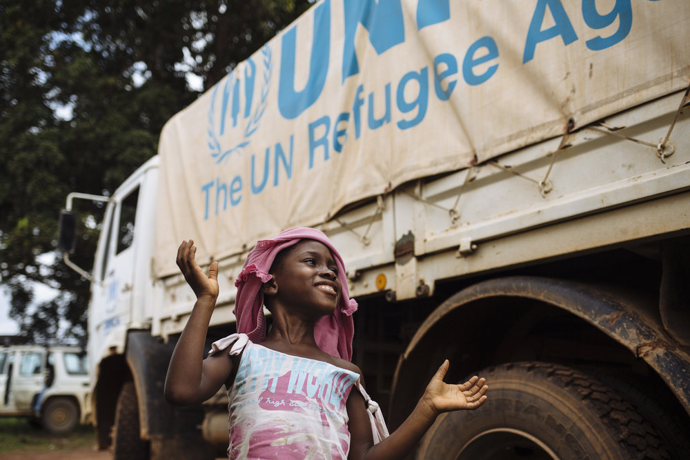 An Ivorian returnee smiles as she walks between UNHCR trucks shortly after a convoy arrived at the UNHCR Voluntary Repatriation Transit Center, Tabou, Bas-Sassandra District, Côte d'Ivoire.