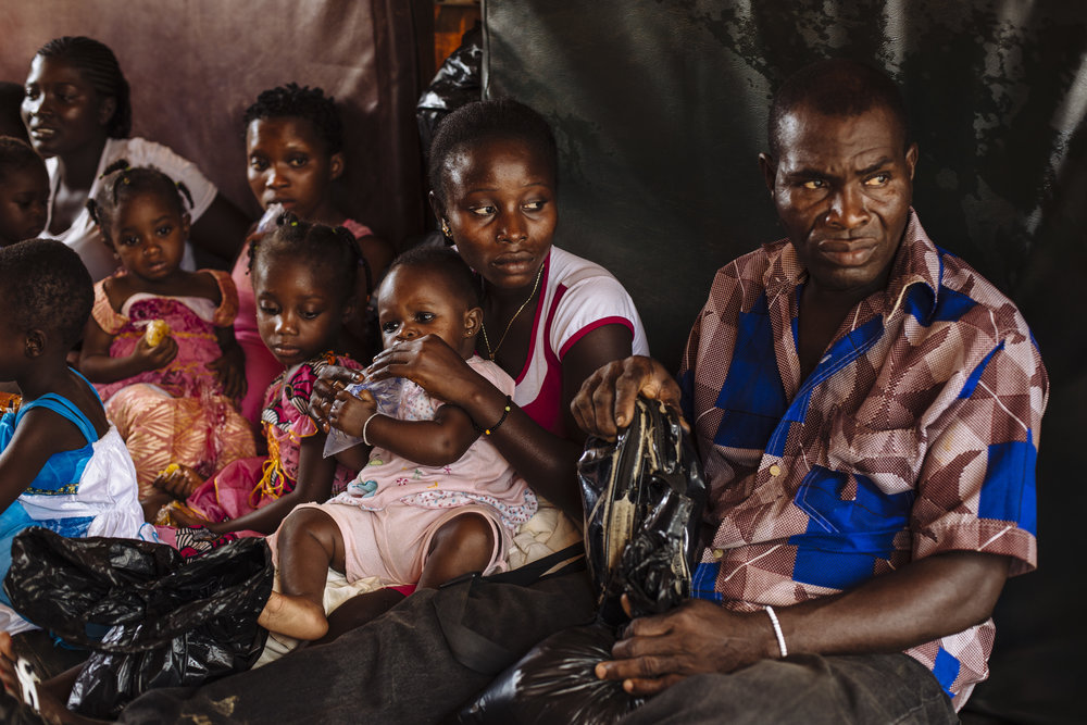 Gbohoun Hie, right, his daughter Yagou Gbordi Hie, and her baby girl Gnepadi Christine Gbohoun and other families sit on mats in a UNHCR truck that will repatriate them to Côte d'Ivoire, in Little Wlebo refugee camp, approximately 15 kilometres (9 miles) from Harper, Maryland, Liberia.