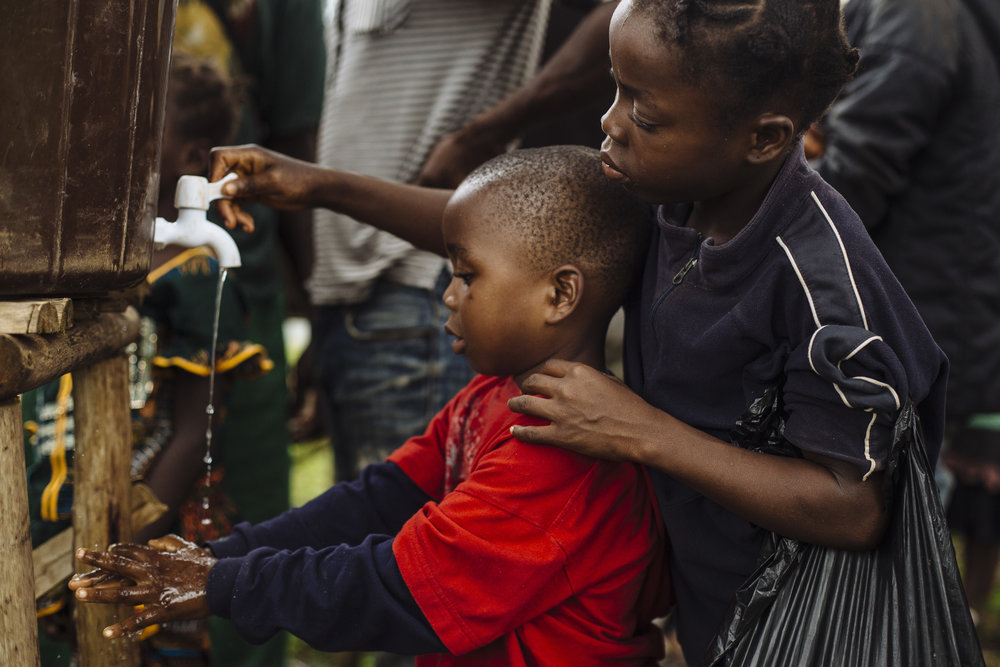 A young girl helps a boy wash his hands as they queue for a health screening, part of efforts to combat the transmission of the Ebola Virus Disease, at a border post near the Cavalla River, which demarcates the border with Côte d'Ivoire, in Maryland, Liberia.