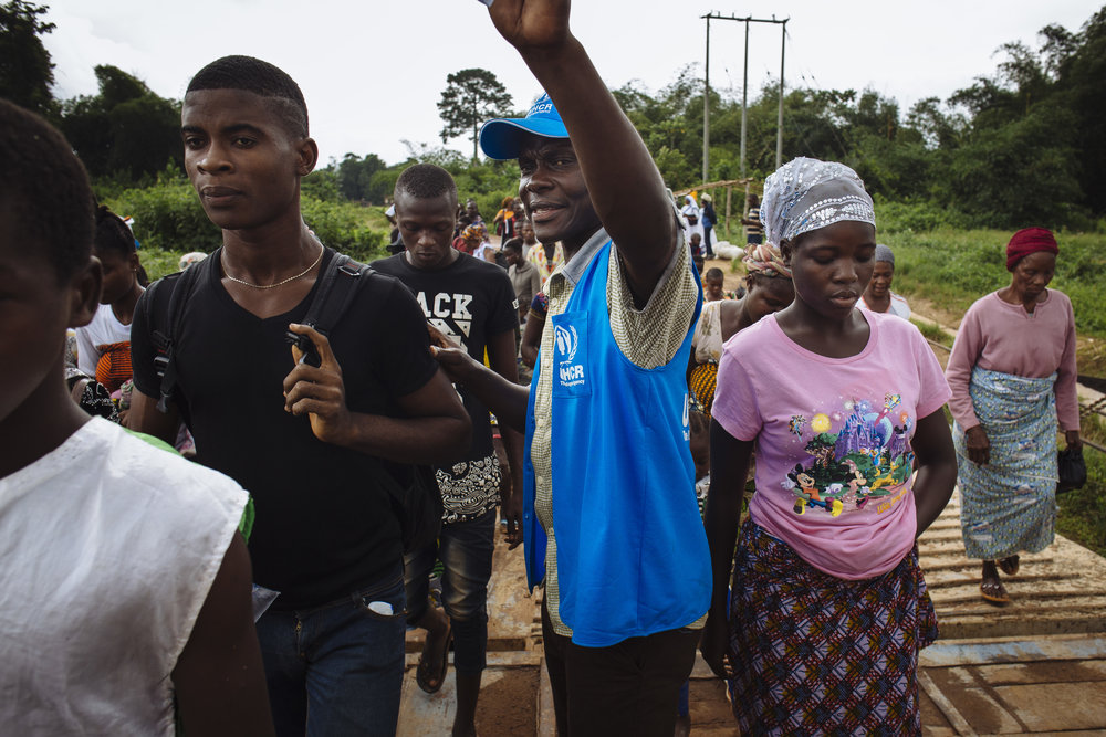 Ivorian refugees are directed by a UNHCR staff member as they board a UNHCR ferry which will take them across the Cavalla River to Côte d'Ivoire, in Maryland, Liberia.